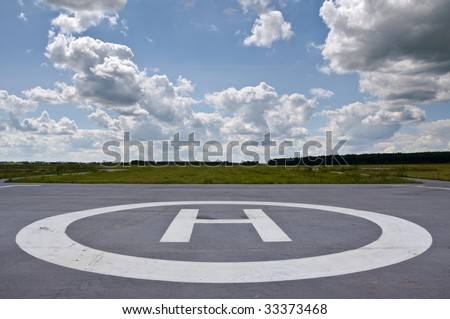 Helipad in the field in cloudy day.