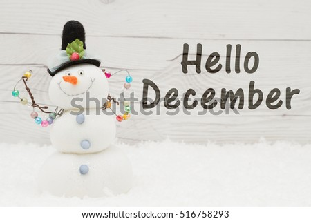 Hello December message, Some snow, Christmas ornaments and a snowman on weathered wood with text Hello December