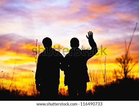 Hello. Two men stand in the background of a beautiful sunset and waving his hand in greeting Hello. Silhouettes in the contre. Special light.