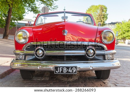 Helsinki, Finland - June 13, 2015: Old red Ford Custom Deluxe Tudor car is parked on the roadside. 1951 year modification with convertible roof, closeup front view