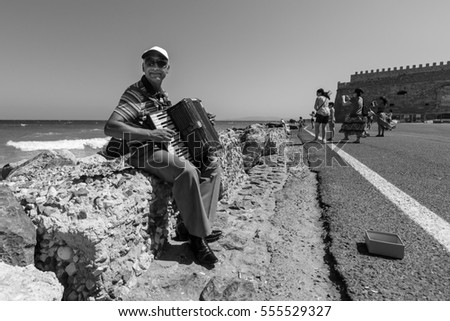 HERAKLION, GREECE - JULY 16, 2016: Crete. Musician on the waterfront plays accordion. In the background Venetian fortress. Black and white.