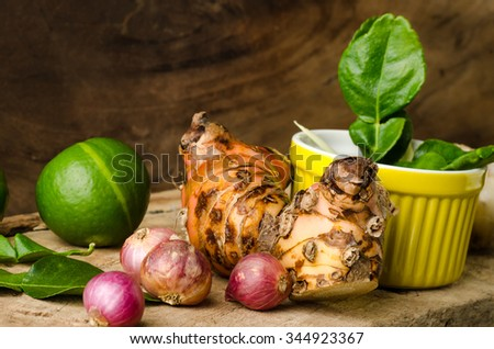 Herb and spice (lime,kaffir lime leaf,shallot and galangal) on wooden background