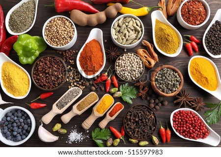 Herbs and spices on dark wooden background. Aromatic ingredients and natural food additives.