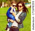 Hi & bye concept. Portrait of fashionable baby boy and his gorgeous mother in trendy sunglasses walking in the street. Mom hugging son. Sunny spring day. Outdoor shot  - stock photo