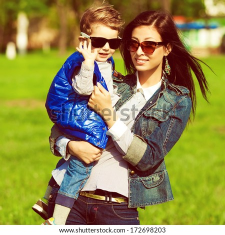 Hi & bye concept. Portrait of fashionable baby boy and his gorgeous mother in trendy sunglasses walking in the street. Mom hugging son. Sunny spring day. Outdoor shot