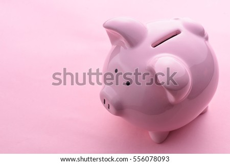 High-angle close-up view of cute piggy bank with copy space on pink background