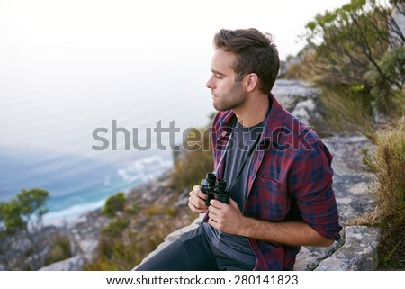 High angle shot of a handsome young man holding binoculars while sitting on a rocky outcrop on a mountain with ocean visible below