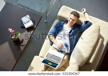 High angle shot of a middle aged man napping on couch at home and listening music.