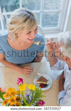 High angle view of a mature man feeding happy woman pastry at home