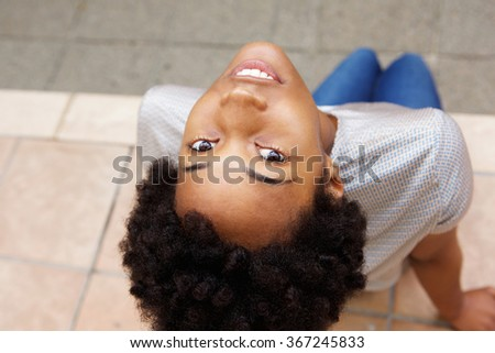 High angle view of beautiful young african woman sitting and looking up