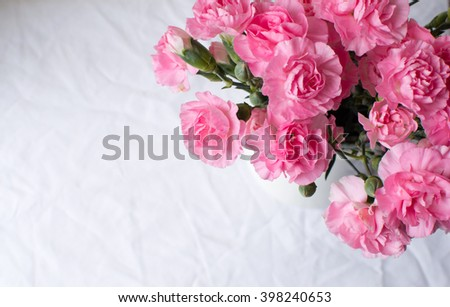 High angle view of pink carnations over white tablecloth