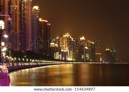 high buldings with neon lighting on coast near Pearl river with color reflections at night in Guangzhou, China