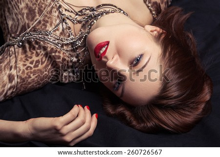 High fashion look. Glamor closeup portrait of beautiful sexy stylish woman model lying on black bed with bright makeup, with red lips, with perfect clean on bed