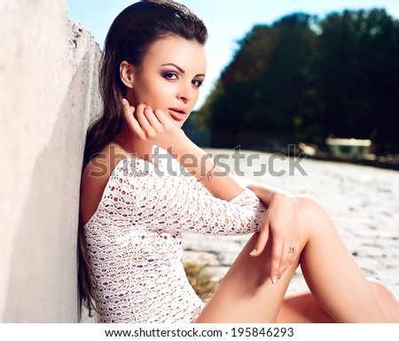 High fashion look.glamour portrait of beautiful sexy pure sensual brunette female model girl in white lingerie .blue sky. sitting outdoors