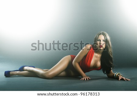 High fashion shot of attractive woman in single piece red lingerie