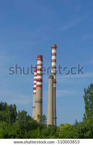 High industrial chimneys in front of green trees with blue sky