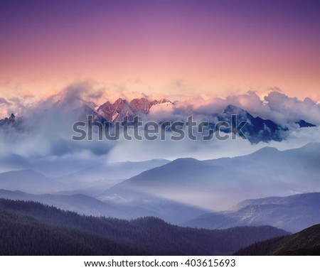High mountain ridge in the clouds during sunrise. Beautiful panoramic landscape