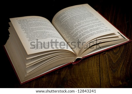 high resolution picture of an old book over a wooden table.