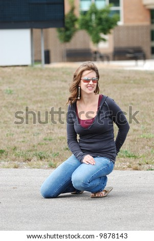 High School Teenage Girl wearing casual clothing, kneeling outdoors.