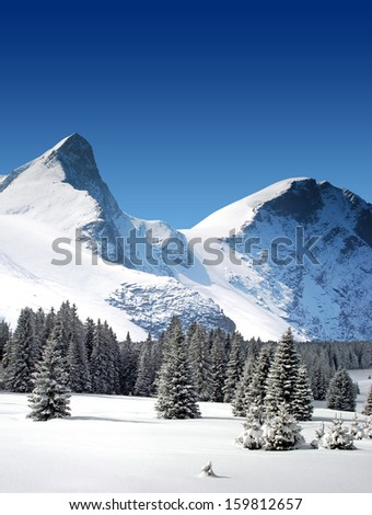 high snowy mountain peaks and glaciers rocks with blue sky