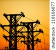high voltage post at sunset. - stock photo