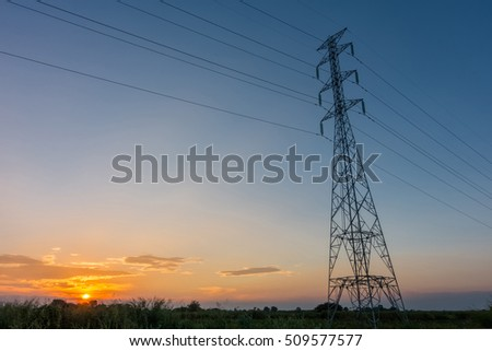 High voltage power pylons in the field at sunset