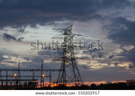 high voltage transmission tower or power tower (electricity pylon) and electrical distribution substation during sunset