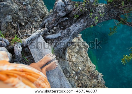 Highly Detailed Photo Woman Legs. Girl Looking Down Cliff Old Tree. Blue Ocean Water Blurred Background.Horizontal picture. Top View Image