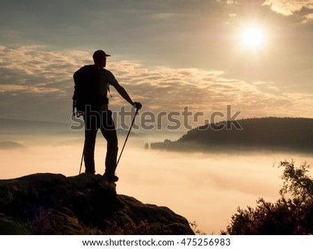 Hiker guide with sporty backpack and poles in hands stand on rocky view point and watching into deep misty valley bellow. Misty spring daybreak in rocky mountains.