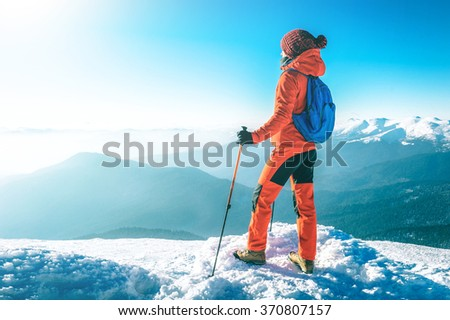 Hiker happy woman trekking on the snow in a snowy mountain in wi