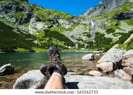 Hiker resting over the glacier lake with a waterfall in the background in high mountains. Taken in High Tatras, Slovakia, Europe.