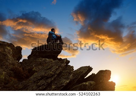 Hiker sitting on the mountain top at sunset.