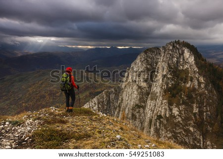Hiker with backpack standing on a rock and enjoying sunset and rays through the clouds