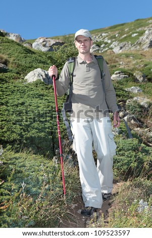 Hiker with trekking poles and backpack on a mountain footpath