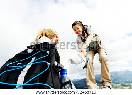 Hiking woman helps her friend climb onto the rock, outdoor lifestyle concept
