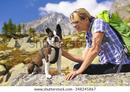 hiking woman with dog Boston Terrier at trail in alps mountains