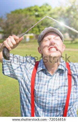 Hilarious Image Of A Distraught And Angry Golfer Bearing His Teeth In Anger And Bending His Golfing Driver In Half After A Huge Miss On A Tee Off In Funny Golf