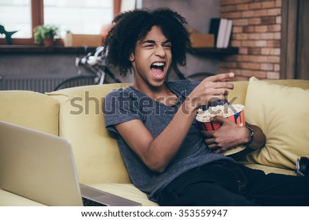 Hilarious TV show. Cheerful young African man watching TV and holding bucket of popcorn while gesturing on the couch at home