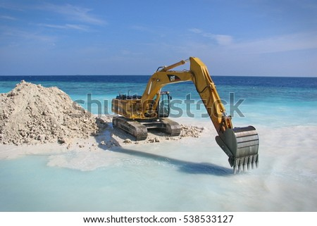 Himandhoo, MALDIVES - December 19, 2014: excavator builds a beach on the sea shore