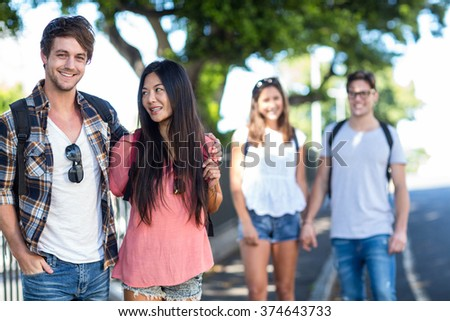 Hip couple with arms around posing for camera in the streets