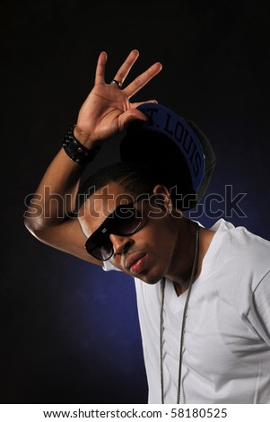 Hip Hop dancer's portrait with hat against a dark background