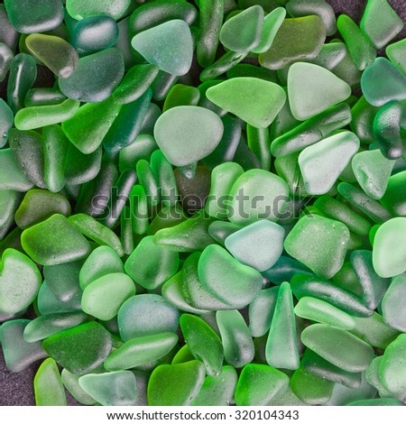 hip of green pieces of glass polished by the sea closeup background