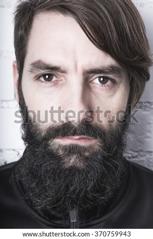 Hipster. Portrait of a bearded young man looking at the camera