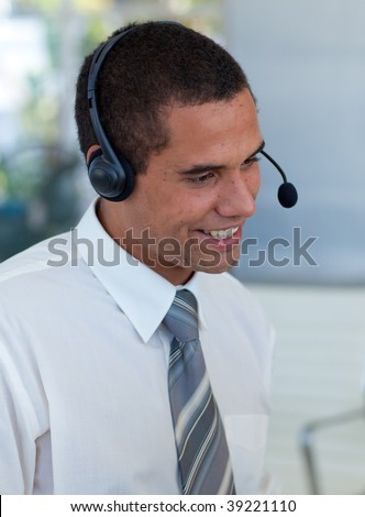 Hispanic businessman with a headset on in a call center