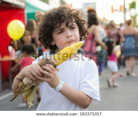 Hispanic child boy eating corn on a cob in a street festival in a city