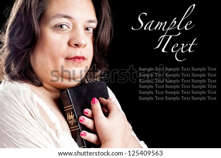hispanic looking woman in a light dress against a black background holding a bible close to her body as she looks up in thought. Sample text to show how your text can be used.