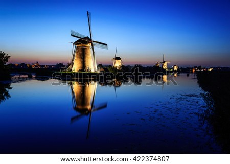 Historic illuminated windmills in Dutch Kinderdijk with reflection in the water of the canal under a Blue Hour sky at dusk, right after sunset in the beginning of the night in the Netherlands.