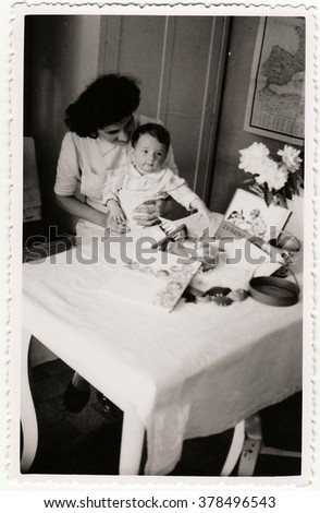 HODONIN, THE CZECHOSLOVAK REPUBLIC - CIRCA 194: A vintage photo shows small toddler girl and her first birthday. Toddler shows cute face.