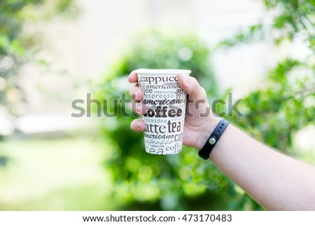 Holding coffee cup in hand
