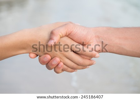 holding hands asian people on the beach